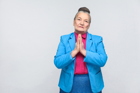 Please forgive me. Emotion and feelings concept. handsome expressive grandmother with light blue suit and pink shirt standing with collected bun gray hair. indoor, isolated on gray background Stock Photo
