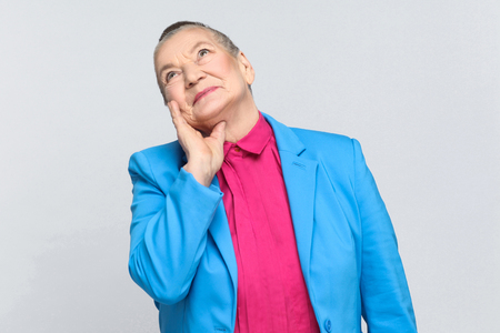 dreaming and imagination of future. Emotion and feelings handsome expressive grandmother with blue suit and pink shirt standing with collected bun gray hair. Studio shot, isolated on gray background