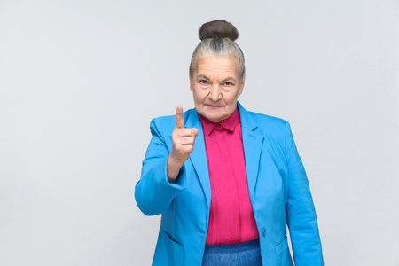 Angry aged woman warning you. Emotion and feelings. emotional expressive grandmother with light blue suit and pink shirt standing with collected bun gray hair. Studio shot, isolated on gray background