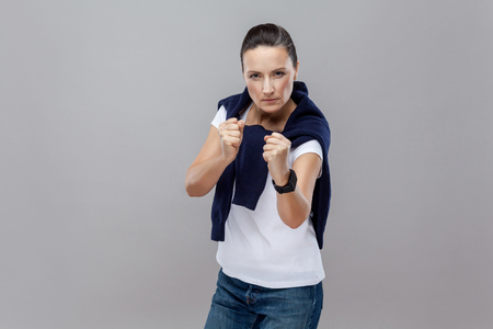 Boxing. Adult woman in casual clothes with blue jeans and sweater on her shoulders, smart watch on arm, ready for fight on grey background. isolated. Studio shot