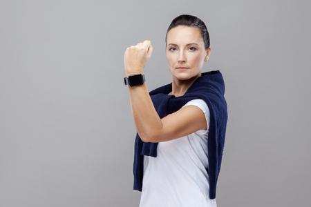 Retrato de mujer morena dominante en ropa casual con jeans y suéter sobre sus hombros mirando seriamente a la cámara mostrando puño y reloj inteligente. aislado, tiro del estudio, fondo gris