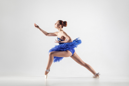 Young beautiful ballerina with bun collected hair wearing blue dress and pointe shoes dancing gracefully isolated on white background. indoor, studio shot. Stock Photo