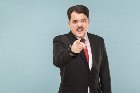 Hey you! Man in suit looking at pointing finger at camera. It's you? I do not believe you lie. indoor studio shot. isolated on blue background. businessman with black suit, red tie and mustache