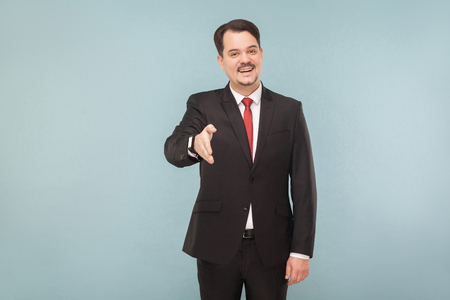 Congratulations you are hired, you will have your office and assistant. indoor studio shot. isolated on blue background. handsome businessman with black suit, red tie and mustache looking at camera. Banco de Imagens