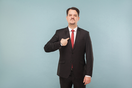 Man in classic wear pointing himself at camera. I did it and Im proud of it. indoor studio shot. isolated on light blue background. handsome businessman with black suit, red tie and mustache.