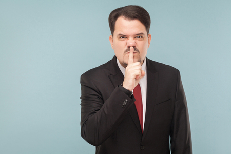 Quiet! There is a meeting, do not make any noise. indoor studio shot. isolated on light blue background. handsome businessman with black suit, red tie and mustache looking at camera with angry face.