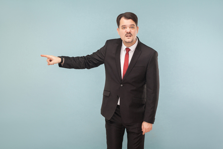You're fired, this was the last mistake. indoor studio shot. isolated on light blue background. handsome businessman with black suit, red tie and mustache looking at camera.