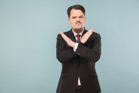Man showing X sign of hands. Bad sign. Do not even try to convince me to do this.. indoor studio shot. isolated on light blue background. handsome businessman with black suit, red tie and mustache.