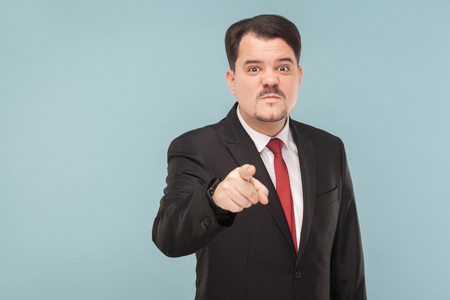 Boss have bad mood. I warn you the last time, Im seriously! indoor studio shot. isolated on blue background. handsome businessman with black suit, red tie and mustache pointing and looking at camera