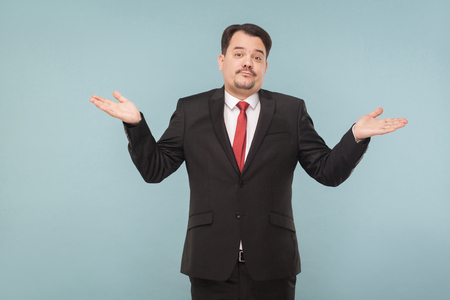 Politican spread his hands to the sides and pretends to be a fool, as if he did not take a bribe. studio shot. isolated on blue background. businessman with black suit and mustache looking at camera Stock fotó