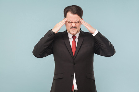 Problems at work, symptoms of disease. Man holding head and have migraine. studio shot. isolated on blue background. handsome businessman with black suit, red tie and mustache. closed eyes.