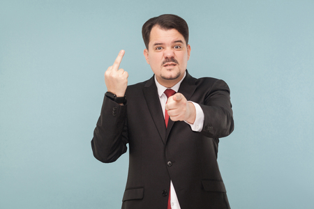 Bad emotions and feelings. Manin suit showing middle finger you sign. indoor studio shot. isolated on blue background. handsome businessman with black suit, red tie and mustache looking at camera