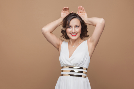 Funny middle aged woman showing rabbit ears and smiling. Emotional expressing woman in white dress, red lips and dark curly hairstyle. Stock Photo