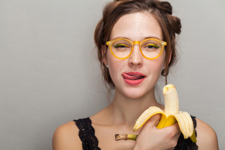 portrait of seductive woman in glasses holding banana and showing tongue out while looking at camera. indoor, studio shot on gray background.