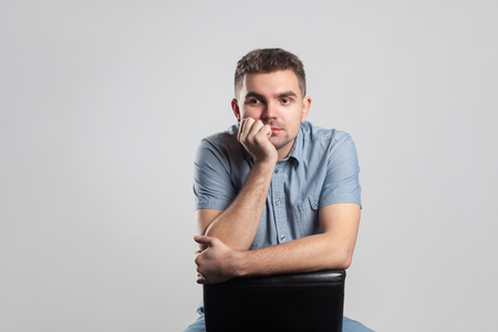 Handsome man sit and thinking. Actors portfolio picture, emotion and feelings. Studio shot, isolated on gray background