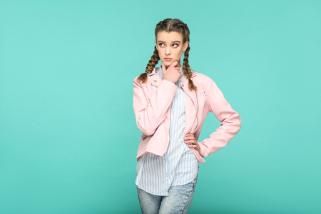 confused thinking portrait of beautiful cute girl standing with makeup and brown pigtail hairstyle in striped light blue shirt pink jacket. indoor, studio shot isolated on blue or green background.