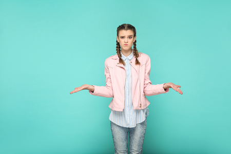 confused doubtful portrait of beautiful cute girl standing with makeup and brown pigtail hairstyle in striped light blue shirt pink jacket. indoor, studio shot isolated on blue or green background. Stock Photo