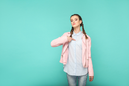 Its me! proud portrait of beautiful cute girl standing with makeup and brown pigtail hairstyle in striped light blue shirt pink jacket. indoor, studio shot isolated on blue or green background.