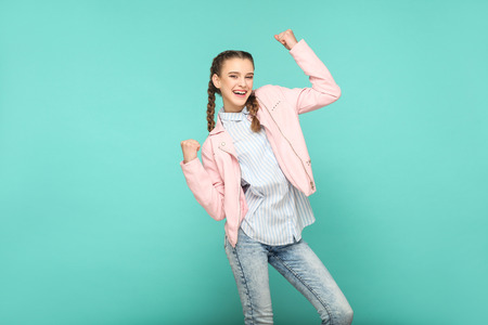 amazed winner portrait of beautiful cute girl standing with makeup and brown pigtail hairstyle in striped light blue shirt pink jacket. indoor, studio shot isolated on blue or green background. Stock Photo