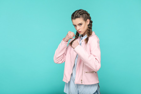 serious attacking portrait of beautiful cute girl standing with makeup and brown pigtail hairstyle in striped light blue shirt pink jacket. indoor, studio shot isolated on blue or green background. Foto de archivo