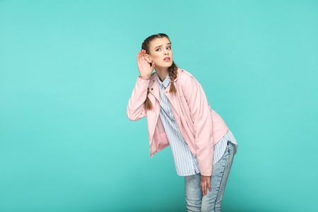 hearing nosy portrait of beautiful cute girl standing with makeup and brown pigtail hairstyle in striped light blue shirt pink jacket. indoor, studio shot isolated on blue or green background.
