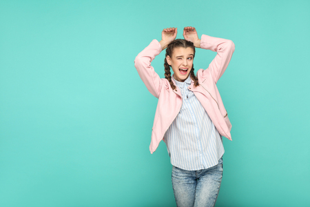 rabbit funny gesture portrait of beautiful cute girl standing with makeup and brown pigtail hairstyle in striped light blue shirt pink jacket. indoor, studio shot isolated on blue or green background.