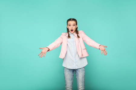 amazed shocked face portrait of beautiful cute girl standing with makeup and brown pigtail hairstyle in striped light blue shirt pink jacket. indoor, studio shot isolated on blue or green background. Imagens