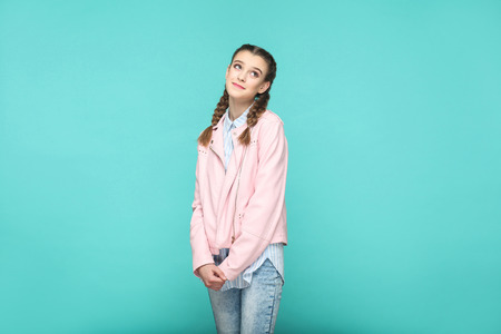 dreaming hopeful portrait of beautiful cute girl standing with makeup and brown pigtail hairstyle in striped light blue shirt pink jacket. indoor, studio shot isolated on blue or green background.