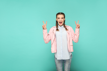 peace or victory portrait of beautiful cute girl standing with makeup and brown pigtail hairstyle in striped light blue shirt pink jacket. indoor, studio shot isolated on blue or green background.