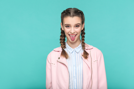 funny tongue out portrait of beautiful cute girl standing with makeup and brown pigtail hairstyle in striped light blue shirt pink jacket. indoor, studio shot isolated on blue or green background.