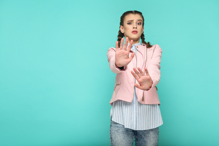 oh no, please stop. portrait of beautiful cute girl standing with makeup and brown pigtail hairstyle in striped light blue shirt pink jacket. indoor, studio shot isolated on blue or green background.
