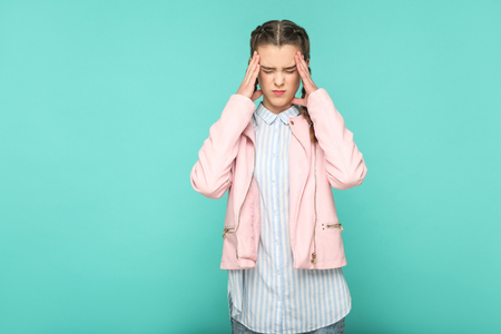 pain or headache portrait of beautiful cute girl standing with makeup and brown pigtail hairstyle in striped light blue shirt pink jacket. indoor, studio shot isolated on blue or green background.