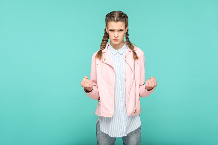 angry sad portrait of beautiful cute girl standing with makeup and brown pigtail hairstyle in striped light blue shirt pink jacket. indoor, studio shot isolated on blue or green background.