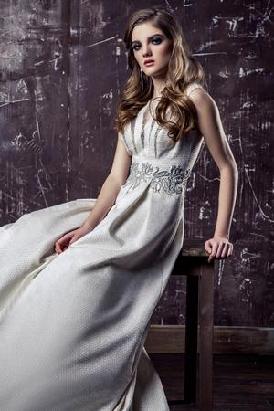 Young model posing in luxury wedding dress, indoor studio shot.