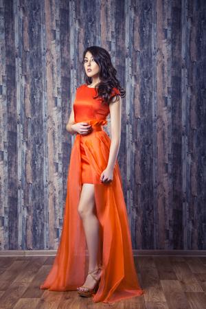Young brunette woman in stylish orange silk dress posing on wooden background Stockfoto