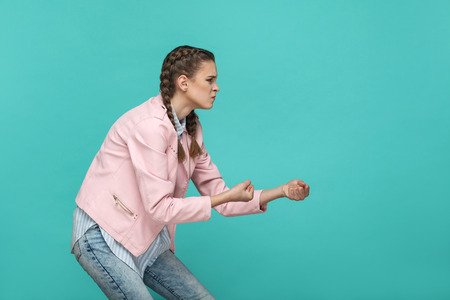side view profile portrait of young serious angry girl in casual style with pink jacket standing and showing pulling gesture or boxing fist. indoor studio shot isolated on green background. Stock Photo