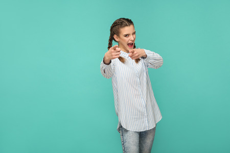now is your time. portrait of funny beautiful girl in blue striped t-shirt and pigtail hair pointing an looking at camera with open mouth and winking. indoor studio shot isolated on green background.