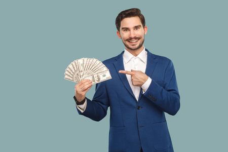 Handsome happy businessman in blue jacket standing and holding many dollars in hand and looking at camera with pointing finger and toothy smile . Indoor, studio shot isolated on light blue background Stock Photo