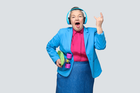 Trendy funny grandmother in casual style with blue headphones holding green skateboard listen music showing rock sign tougue out, looking at camera. Indoor, studio shot, isolated on gray background Stockfoto