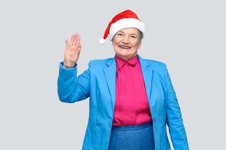 Hi, nice to see you. happy toothy smiling colorful casual style aged woman with blue suit and christmas santa red cap standing and looking at camera. indoor, studio shot, isolated on gray background Stock Photo