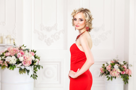 beautiful richly lady standing and posing in red dress and jewelry with hands on waist. Looking at camera, indoor, Studio shot