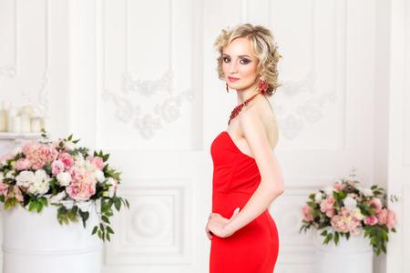 schöne reiche Dame stehend und posierend in rotem Kleid und Schmuck mit Händen auf Taille. Blick auf Kamera, Innen, Studioaufnahme