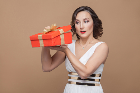 Cunning middle aged elegant brunette woman in white dress holding and looking inside the red gift box. Emotion and feeling concept. Studio shot, indoor, isolated on light brown background Stock Photo