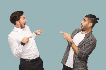 Is that you? profile side view of two handsome funny wondered bearded friends standing and pointing to each other with amazed face and asking. indoor studio shot, isolated on light blue background.