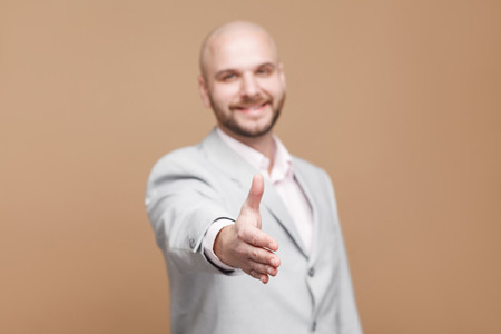 Nice to meet you. happy toothy smiling handsome middle aged bald bearded businessman in classic gray suit standing and giving handshake. indoor studio shot, isolated on light brown background.