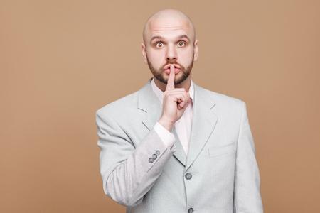 shhh das ist geheim. Porträt des schönen kahlen bärtigen Geschäftsmannes mittleren Alters im klassischen hellgrauen Anzug stehend und betrachten Kamera mit Schweigezeichen. Innen isoliert auf hellbraunem Hintergrund.