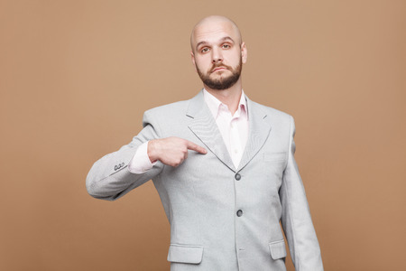 Yes I am. serious proud handsome middle aged bald bearded businessman in classic light gray suit standing looking at camera, pointing himself and prouding . studio shot, isolated on brown background 写真素材