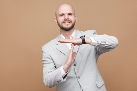 please I need more time. Middle aged bald bearded businessman worker in classic light gray suit standing looking at camera and asking for timeout. indoor studio shot, isolated on brown background.