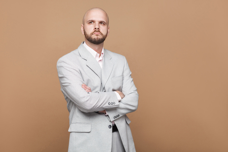 Portrait of confused handsome middle aged bald bearded businessman in classic light gray suit standing and thinking with crossed hands. indoor studio shot, isolated on light brown background. 写真素材