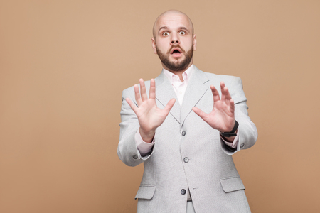 Portrait of scared stressed middle aged bald bearded businessman in classic light gray suit standing and looking at camera with shocked face. indoor studio shot, isolated on light brown background. Фото со стока